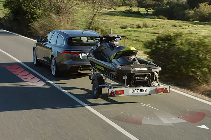 Jaguar XF Driving Down Road Towing A Jet Ski On A Trailer With The Deployable Towbar.