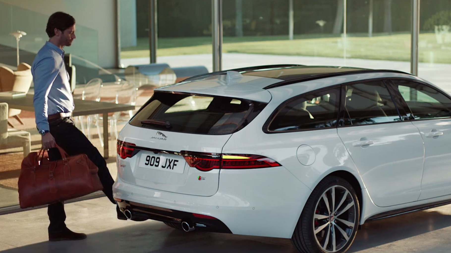 Jaguar XF gesture tailgate feature being demonstrated by a man.