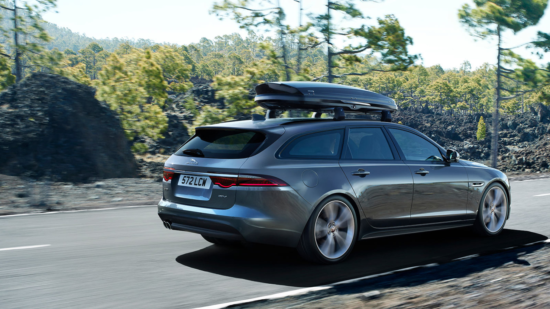 A Jaguar XF Sportbrake driving along a road with a fitted roofbox.