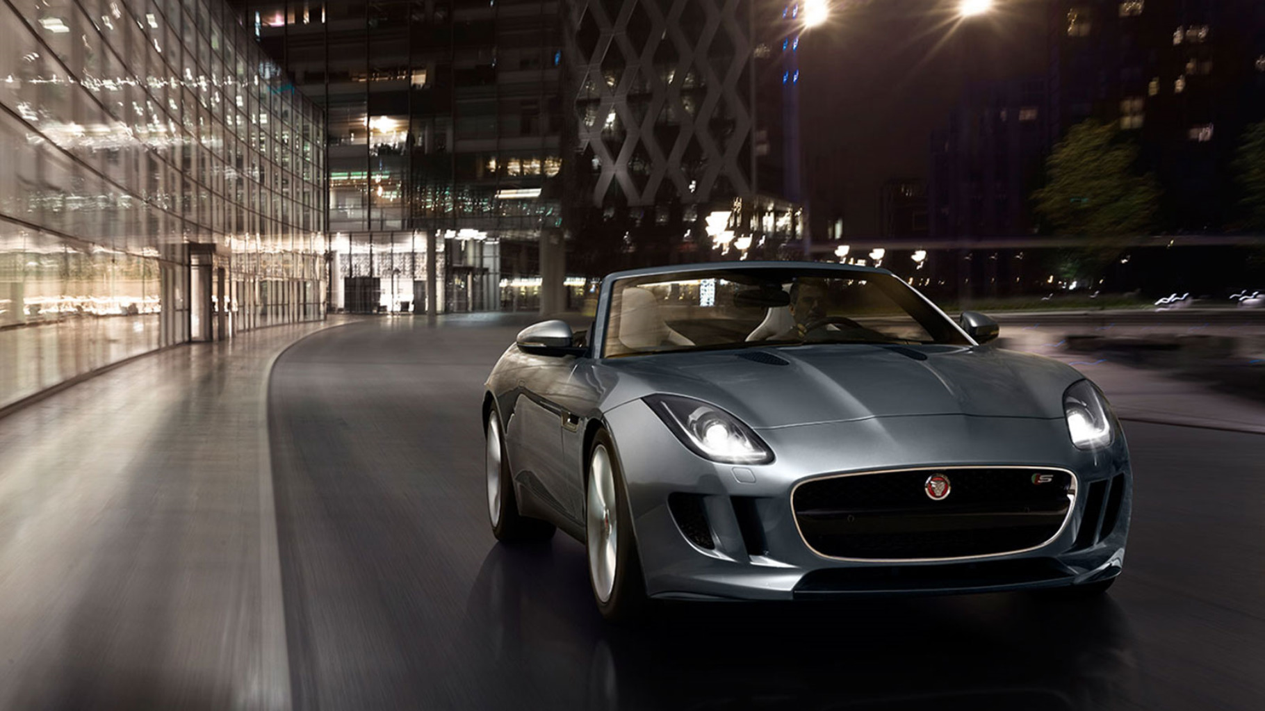 F-TYPE parked next to building at night.