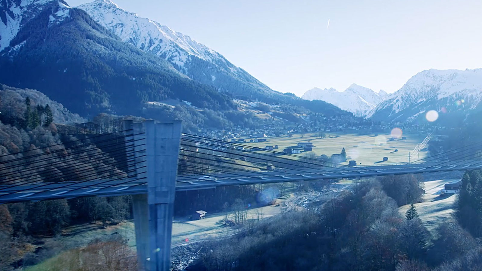 Video still of mountainous area, with bridge in the foreground.