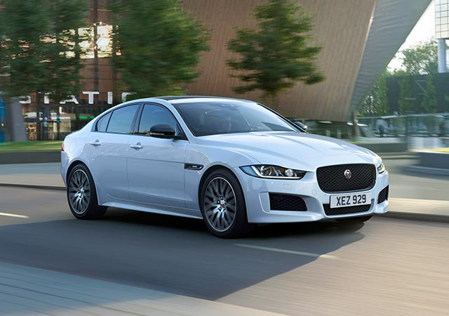 White Jaguar XE Landmark driving on city road
