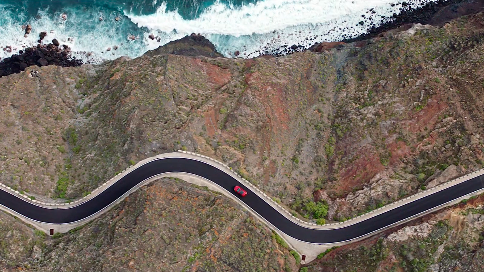 Aerial view of Jaguar E-Pace driving down a winding road.