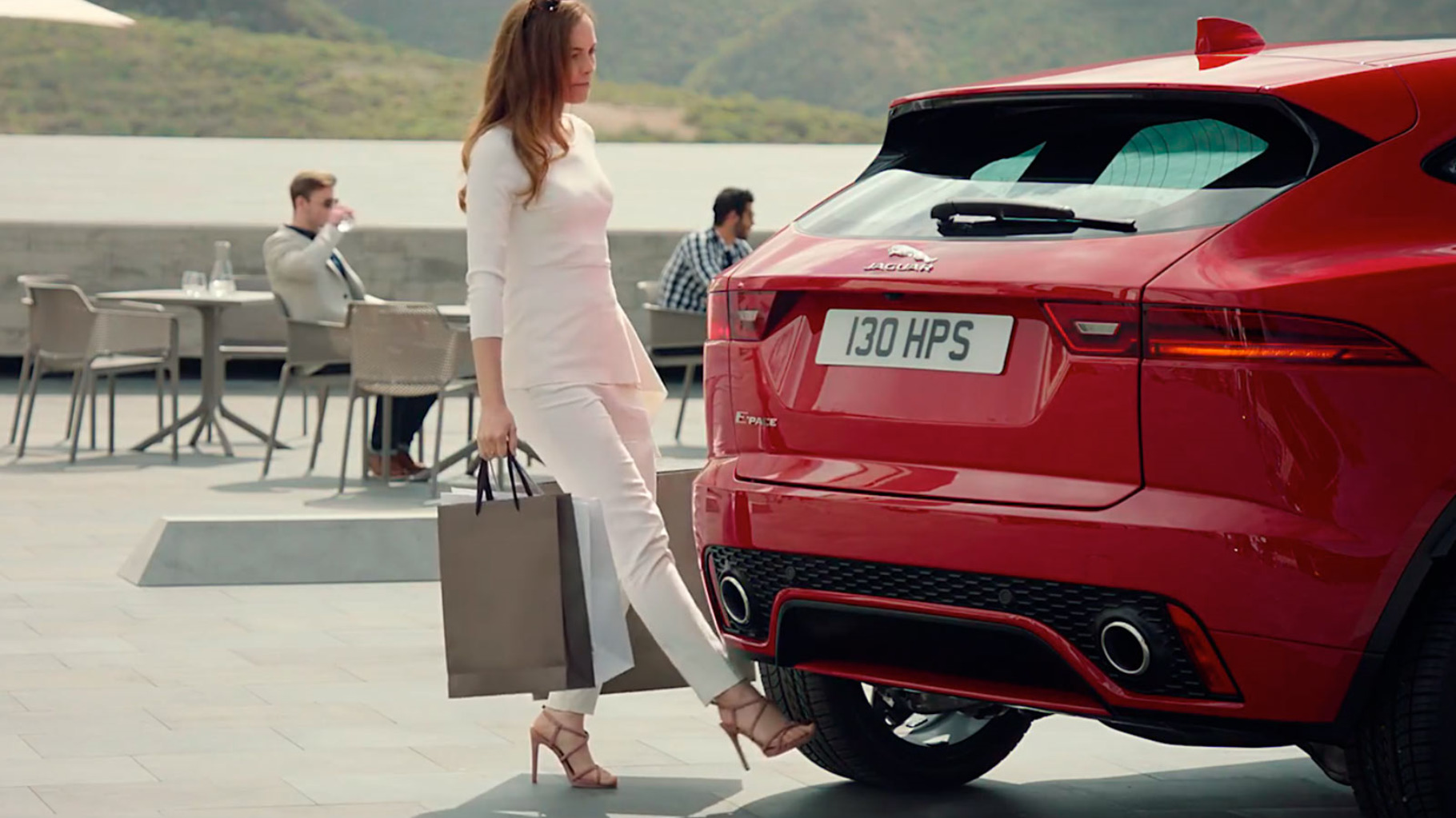 Woman holding bags using her foot to activate the Jaguar E-Pace Gesture Controlled Tailgate.