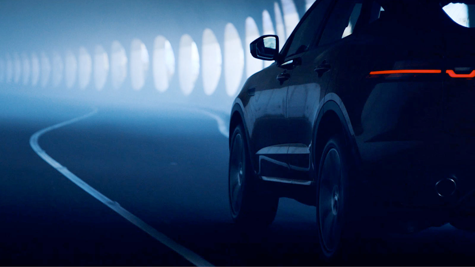 Jaguar E-PACE driving through darkened tunnel.