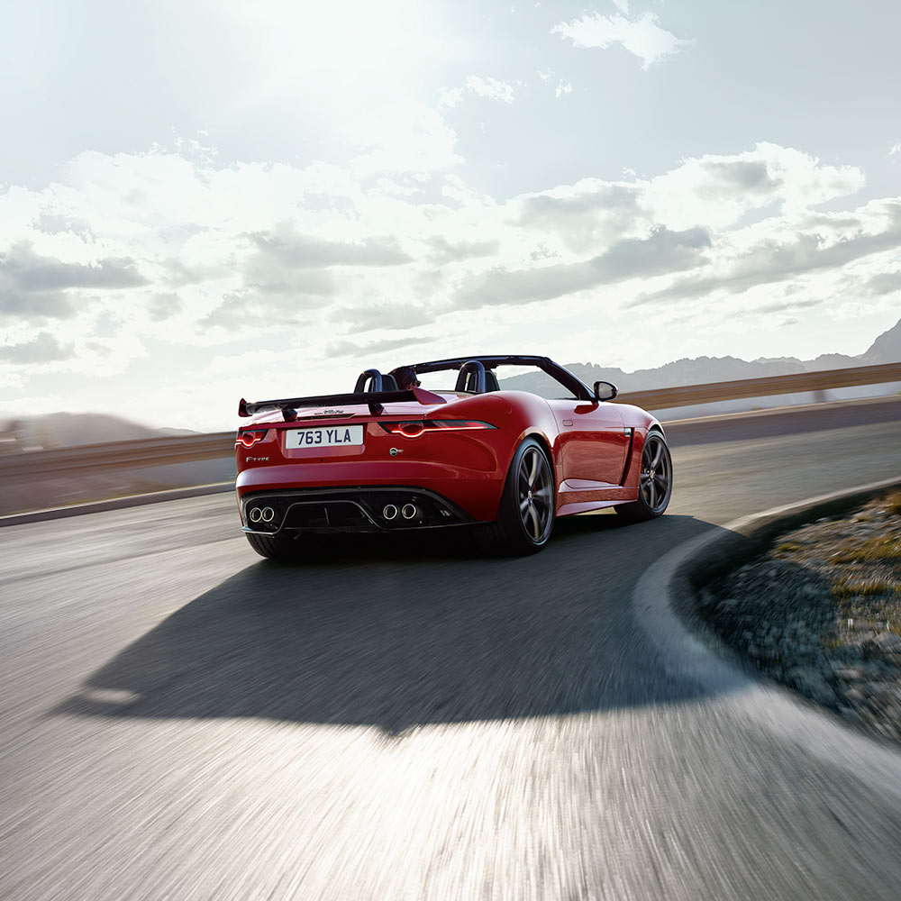 Jaguar F-Type Convertible driving around a curved road.