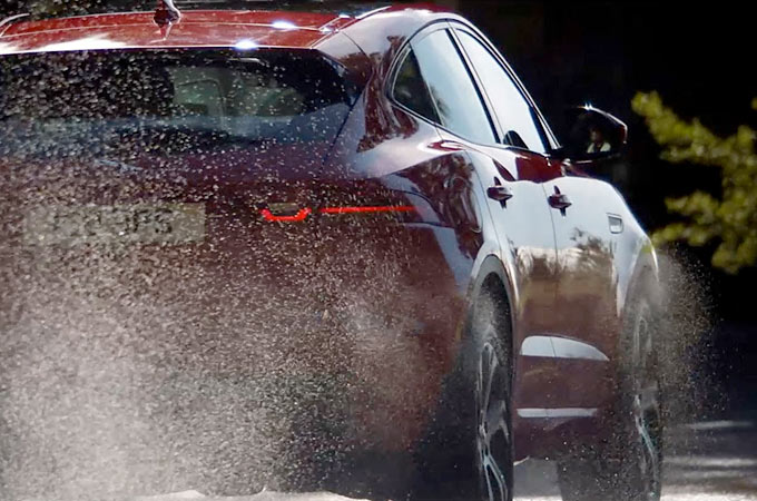 Jaguar E-Pace driving off road through forest.