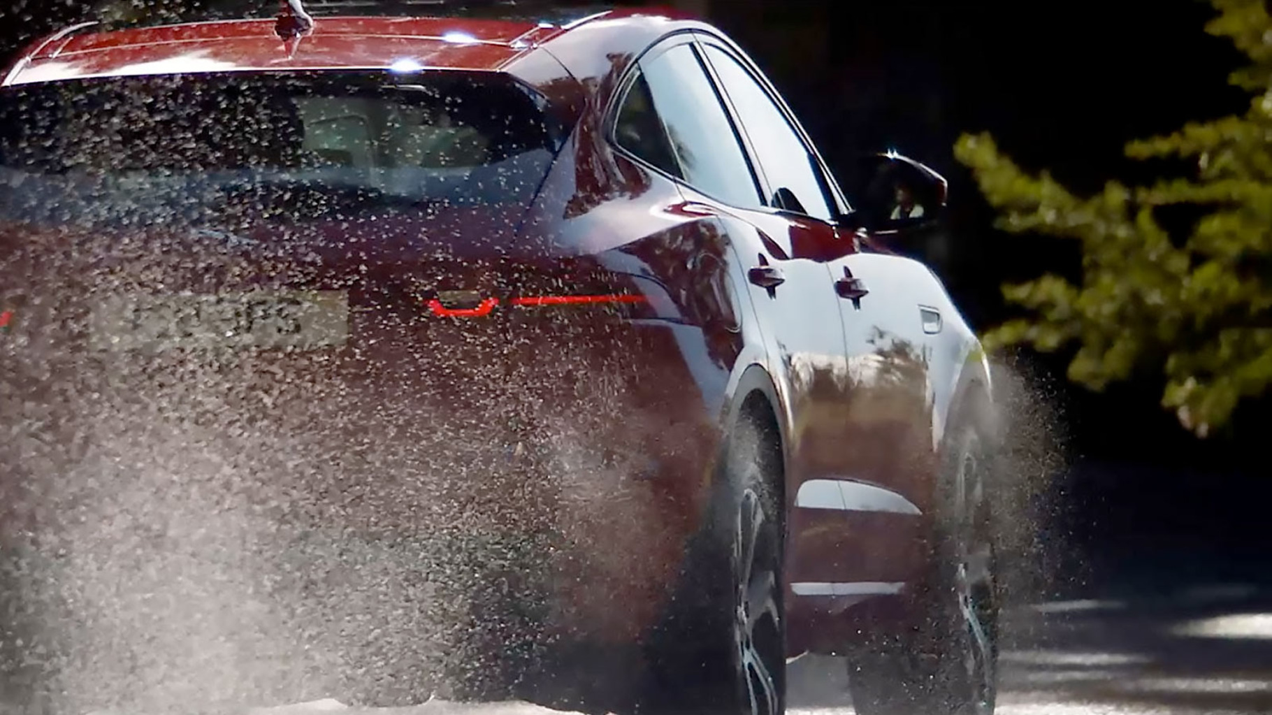 Jaguar E-Pace driving off-road through a forest track.