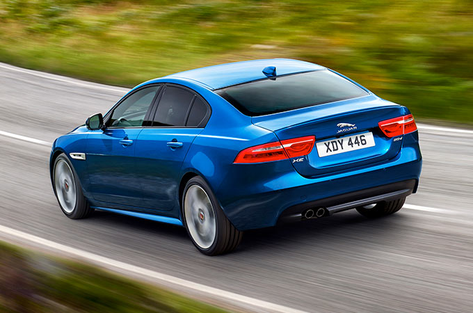 Jaguar XE driving on a winding road.
