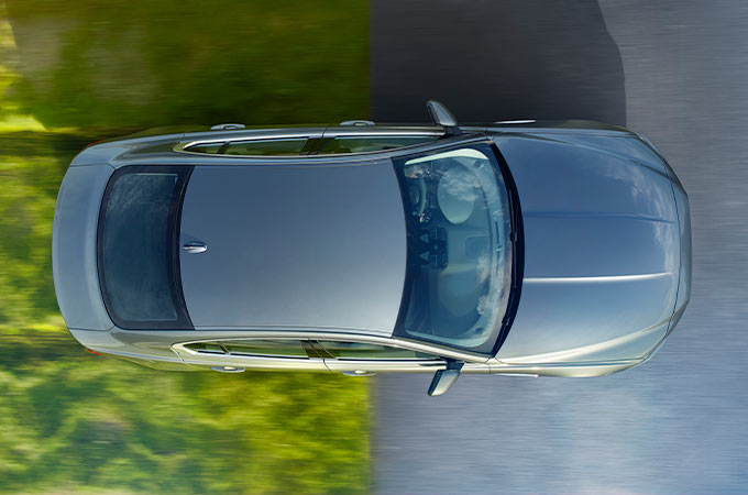 Jaguar XE, from above, driving from grass to tarmac.