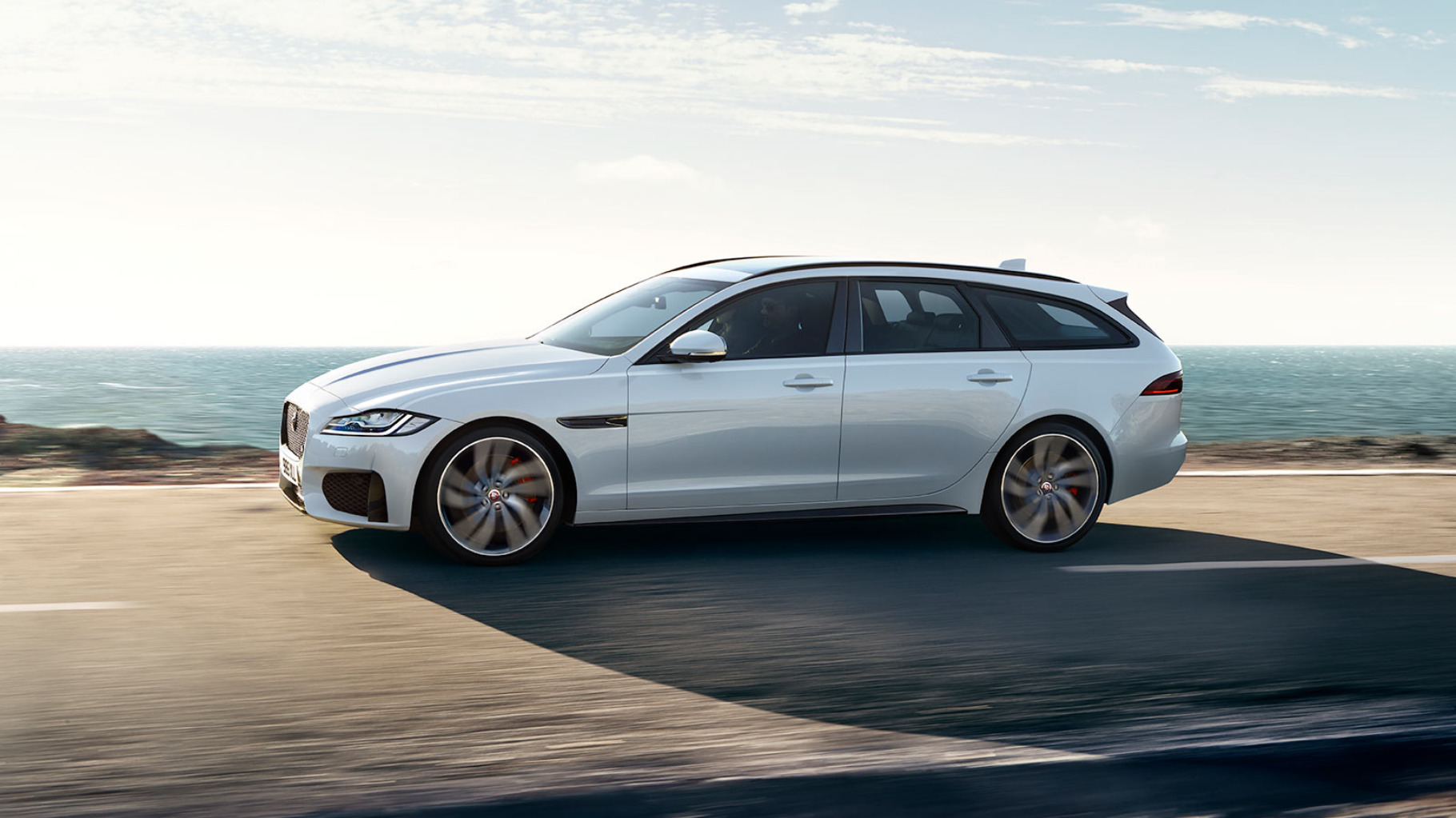 A Jaguar XF Sportbrake driving along a road.