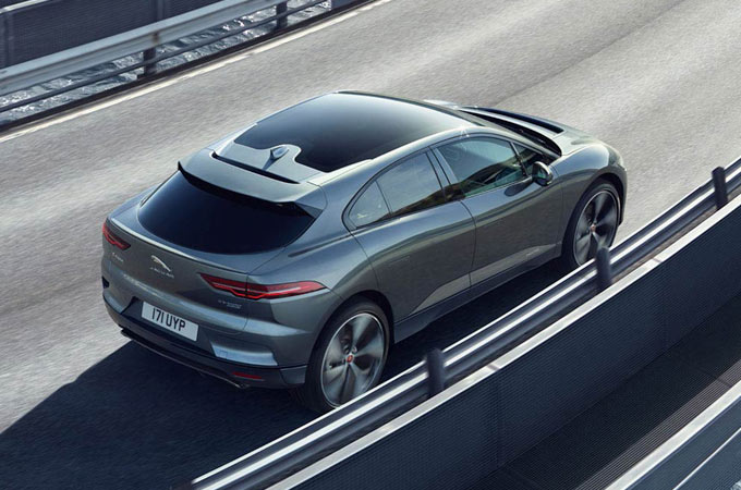 Jaguar I-Pace Driving down a road.