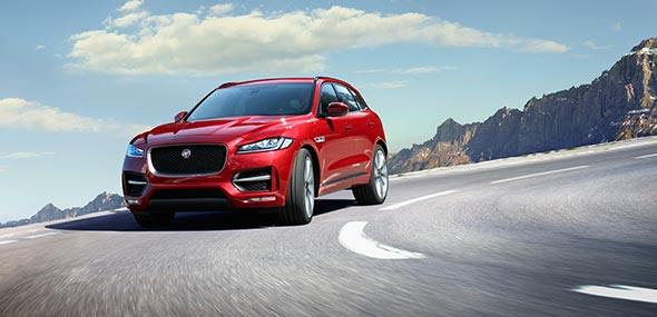 Red Jaguar F-PACE driving on road