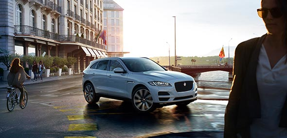 White Jaguar F-PACE driving on road with safety features