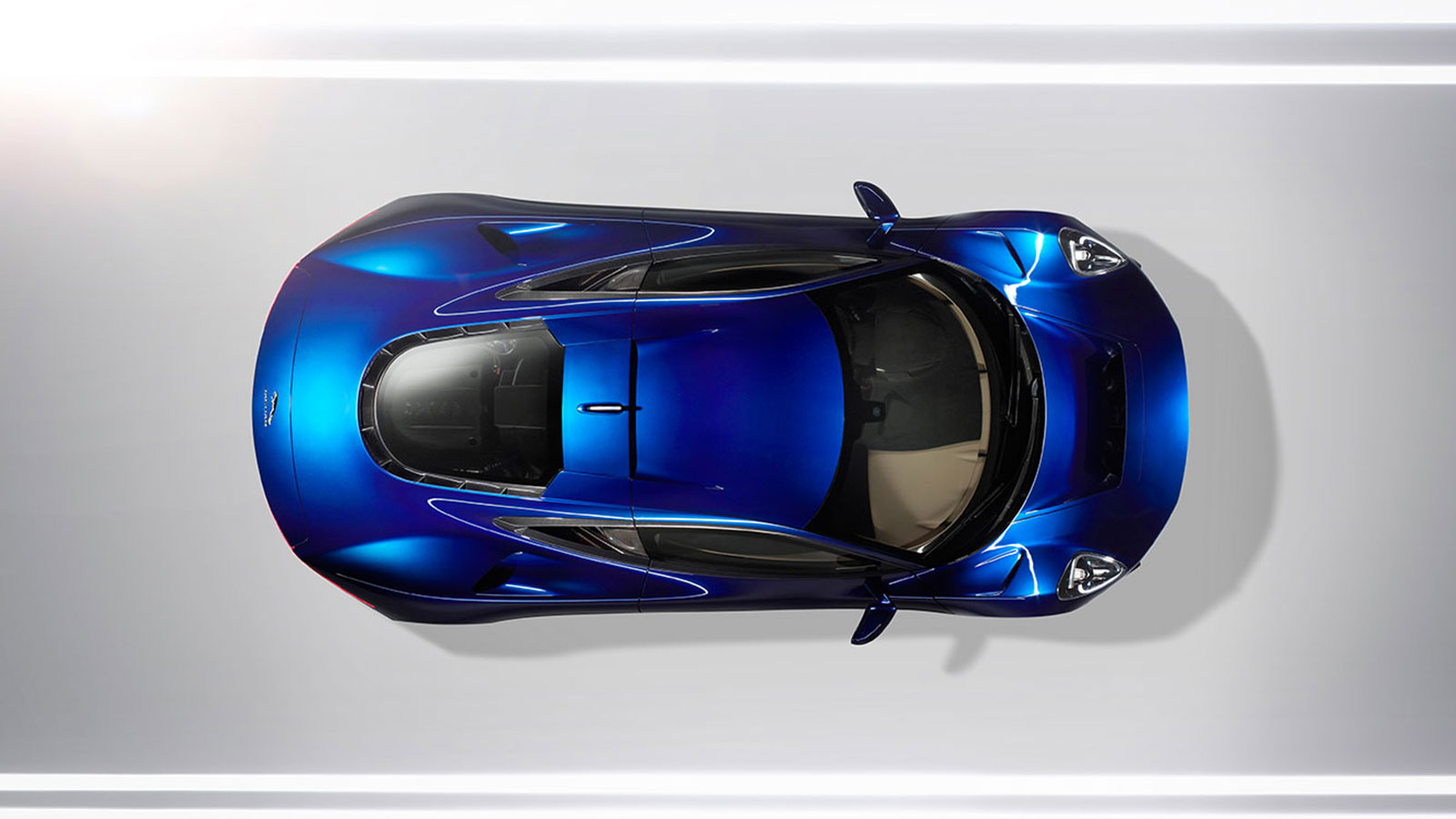 Above shot of Blue Jaguar C-X75 parked within a white studio.