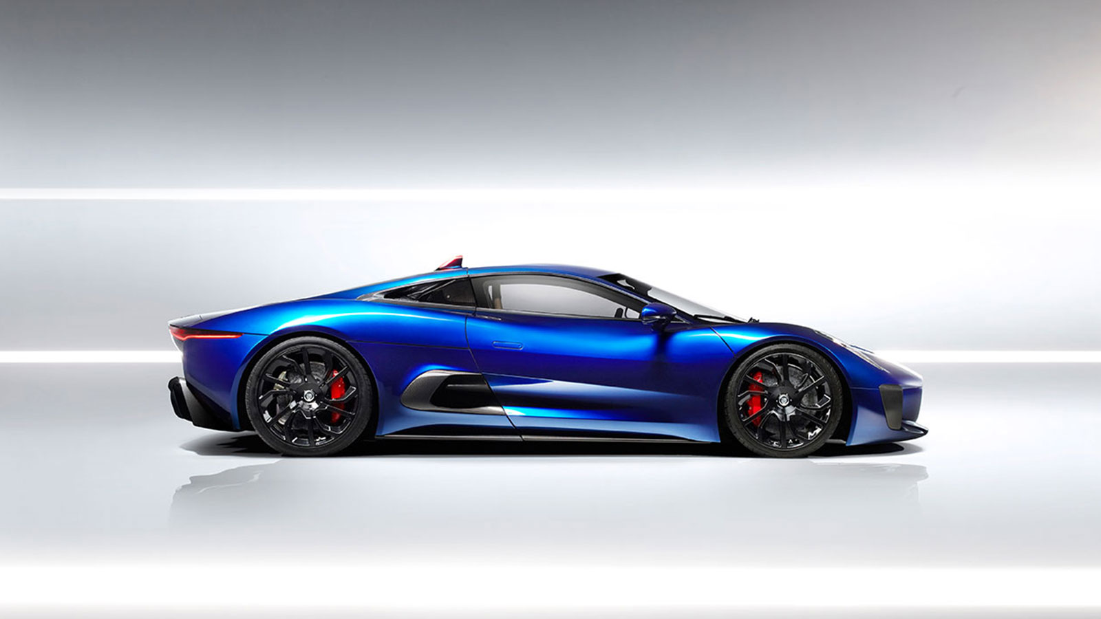 Blue Jaguar C-X75 parked within a white studio.