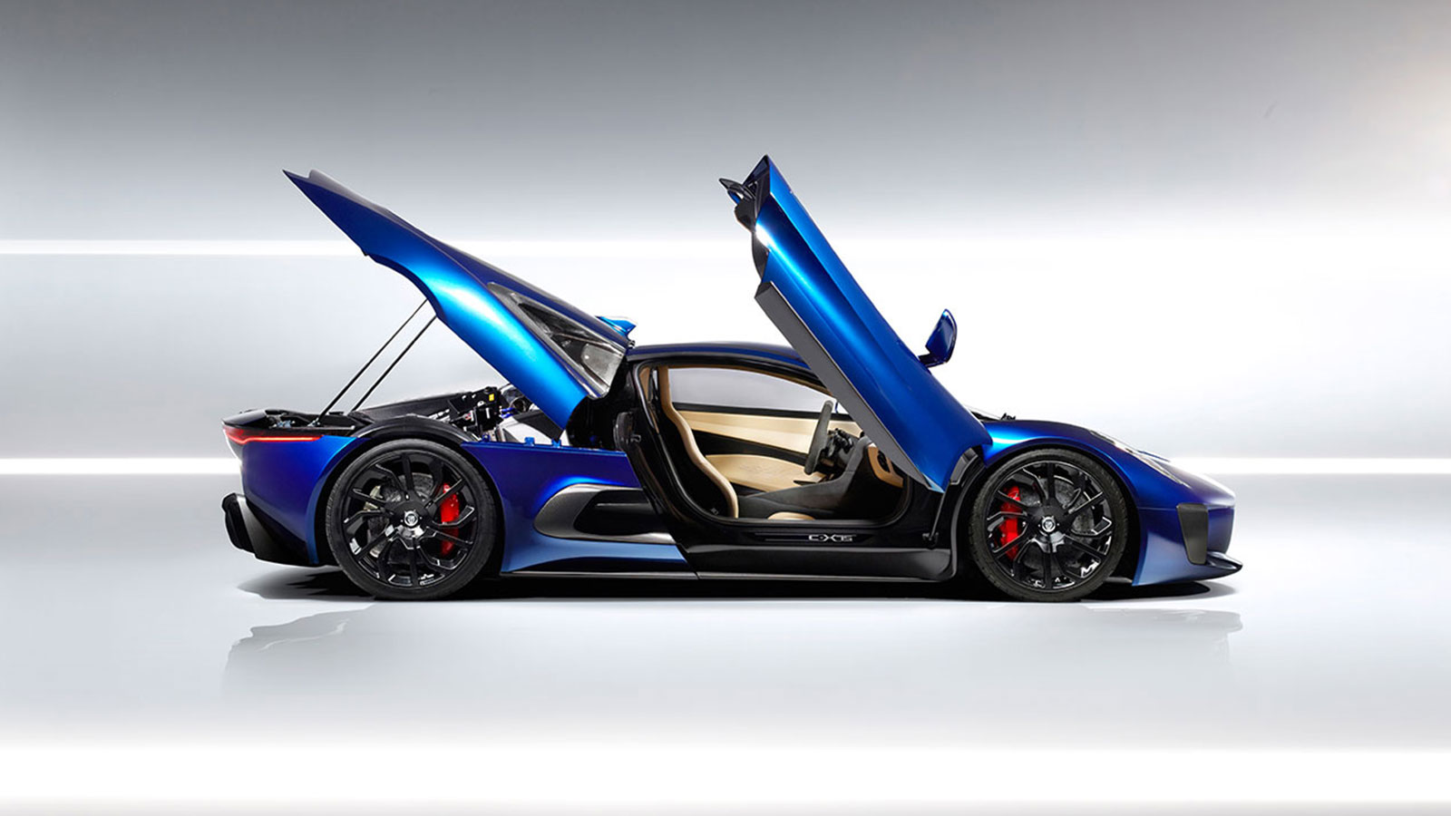Blue Jaguar C-X75 parked within a white studio with doors open.