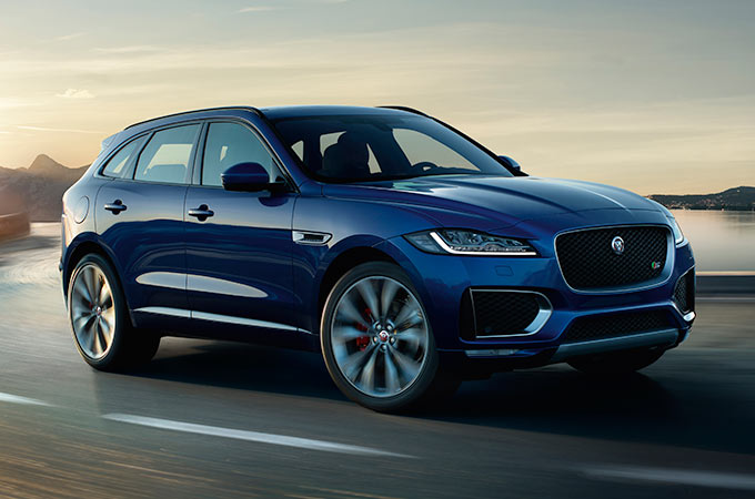 Jaguar F-PACE in blue driving along a road.