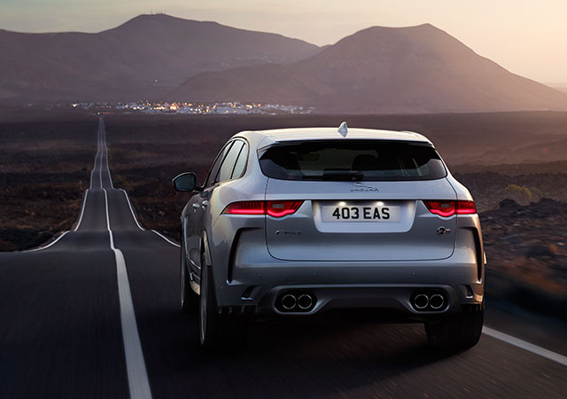 Rear View of Grey Jaguar F-PACE SVR driving on desert open road