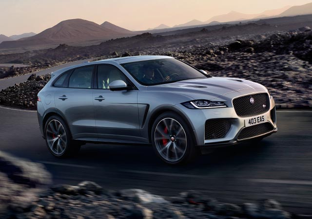 Grey Jaguar F-PACE driving around a bend desert open road