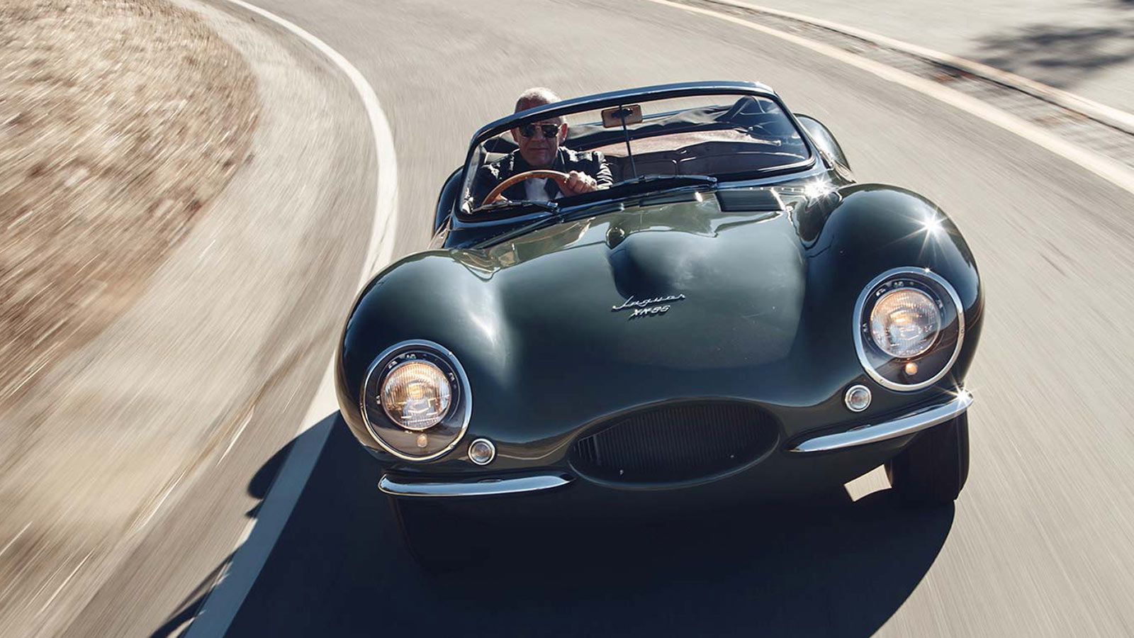 Jaguar XKSS in green driving round a bend.