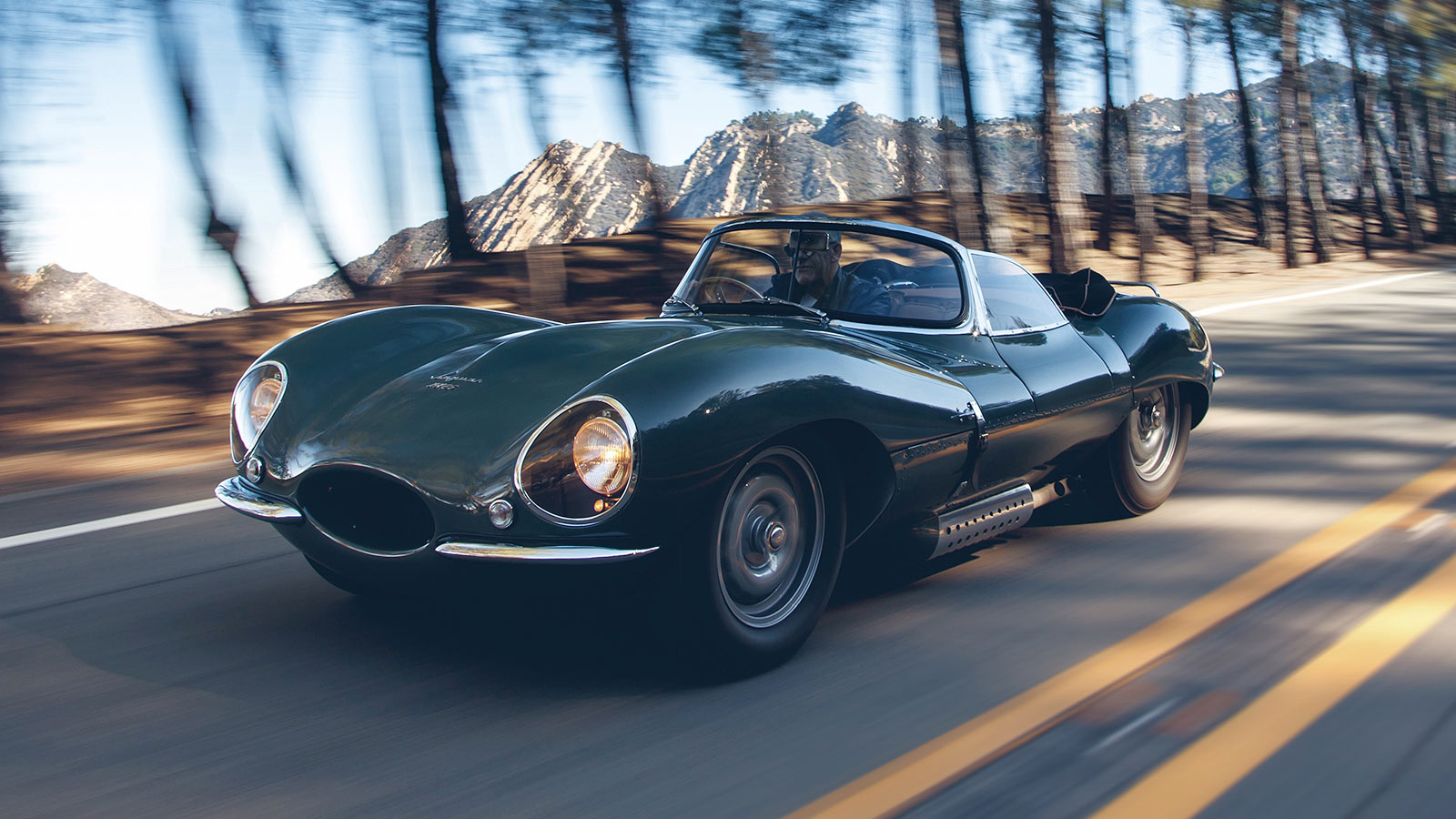 Jaguar XKSS in green driving down a road.