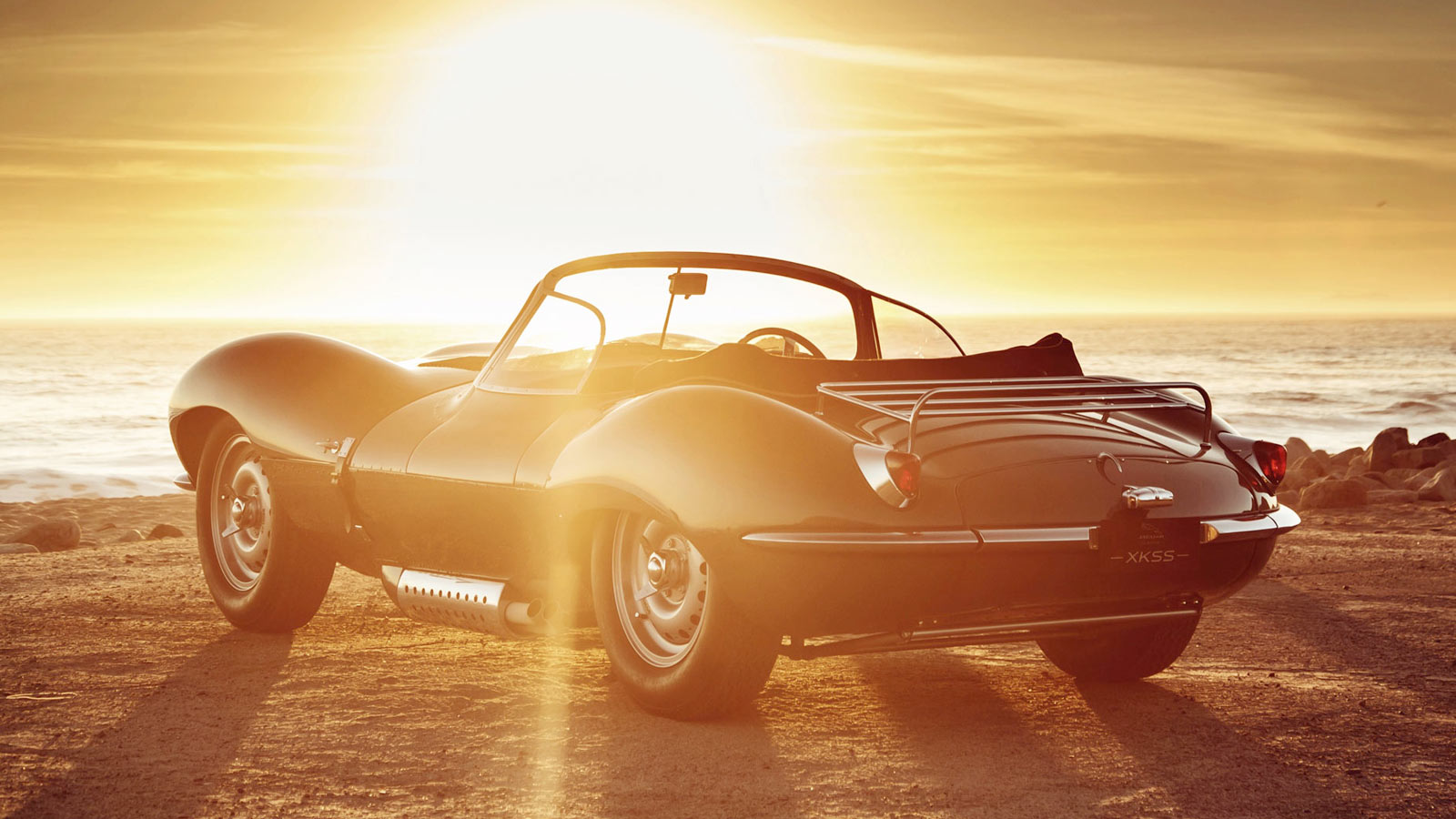 Jaguar XKSS facing the sea at sunset.