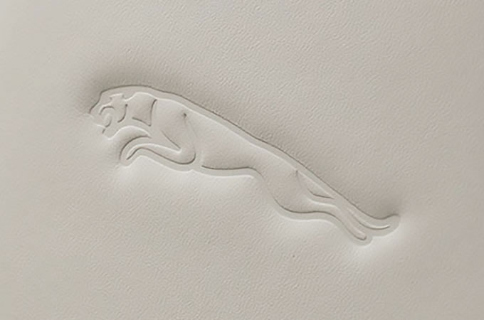 Cream headrest with leaper embossing.