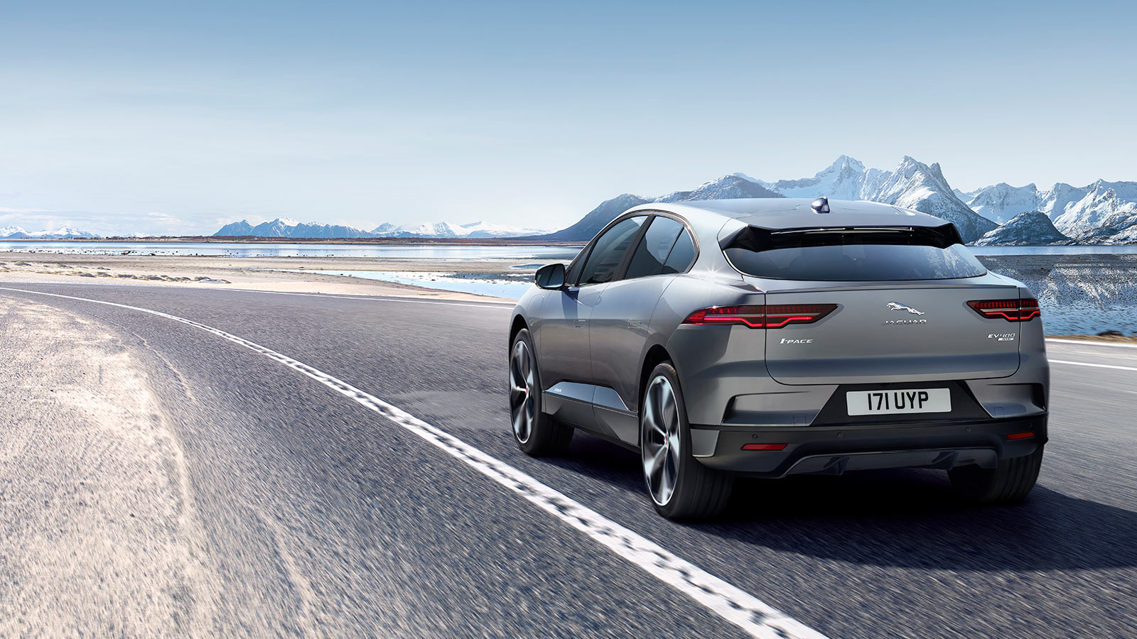 Jaguar I-Pace driving through a road surrounded by rough terrain.