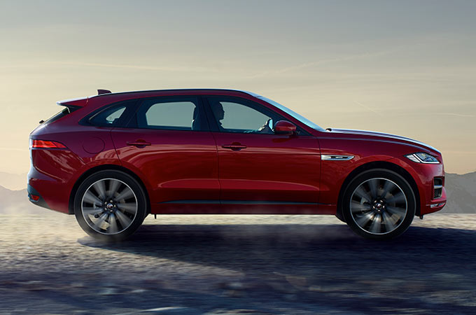 Side view of a red Jaguar F-PACE, driving along rough terrain.