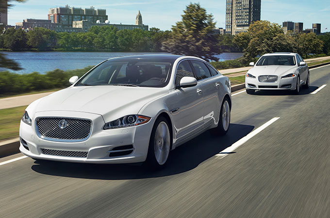 Two Jaguar XJ's in white driving on a road by a lake.