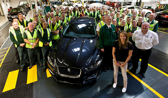 Jaguar employees in visibility jackets surrounding a Jaguar model.