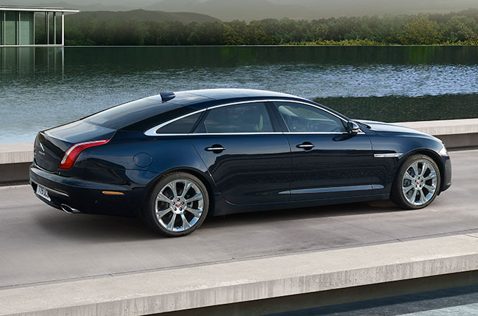 Jaguar XJ Driving On Road Near Water.