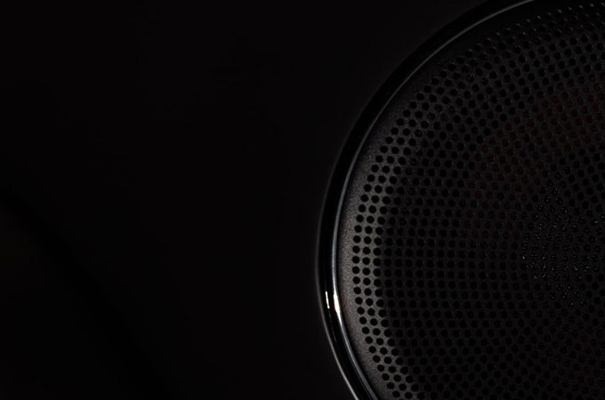 Black speaker cover with dimples in the black background.