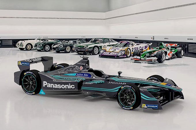 Jaguar Racing Formula E Car in a show room with older Jaguar Cars in the background.