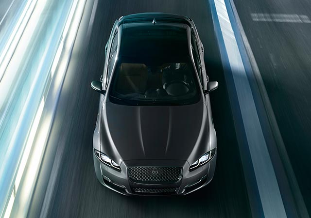 Grey Jaguar XJ driving on road
