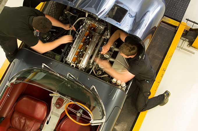 Two mechanics working on the engine of a classic vehicle.