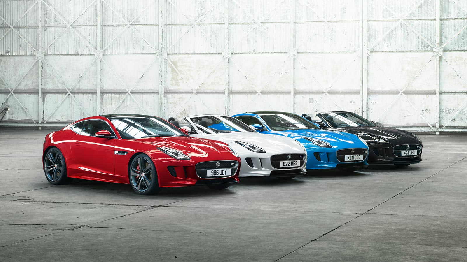A selection of F-TYPE British Design Edition cars in different colours inside an aircraft hangar.