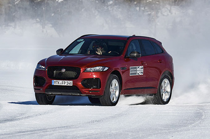 red jaguar driving on snow.
