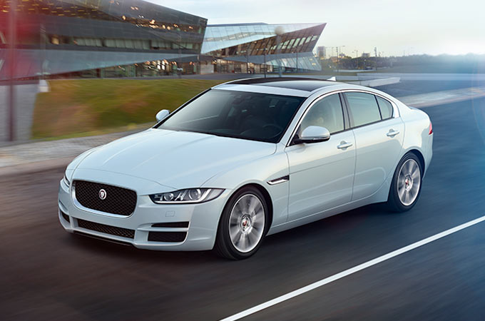 Jaguar XE driving down a road.
