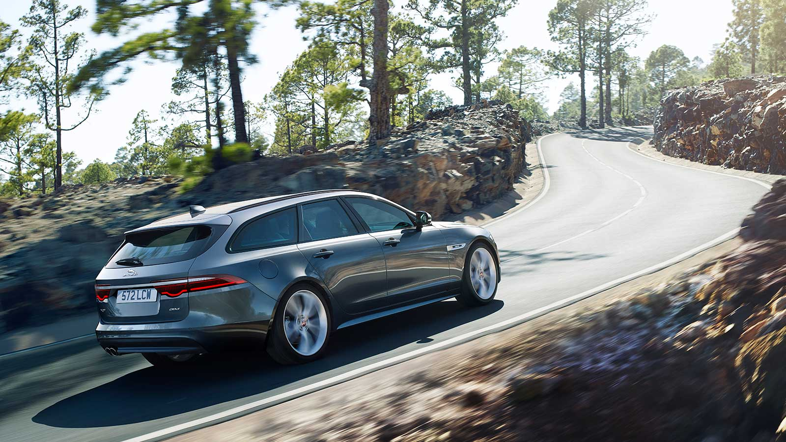 Jaguar XF driving uphill on a mountain road.