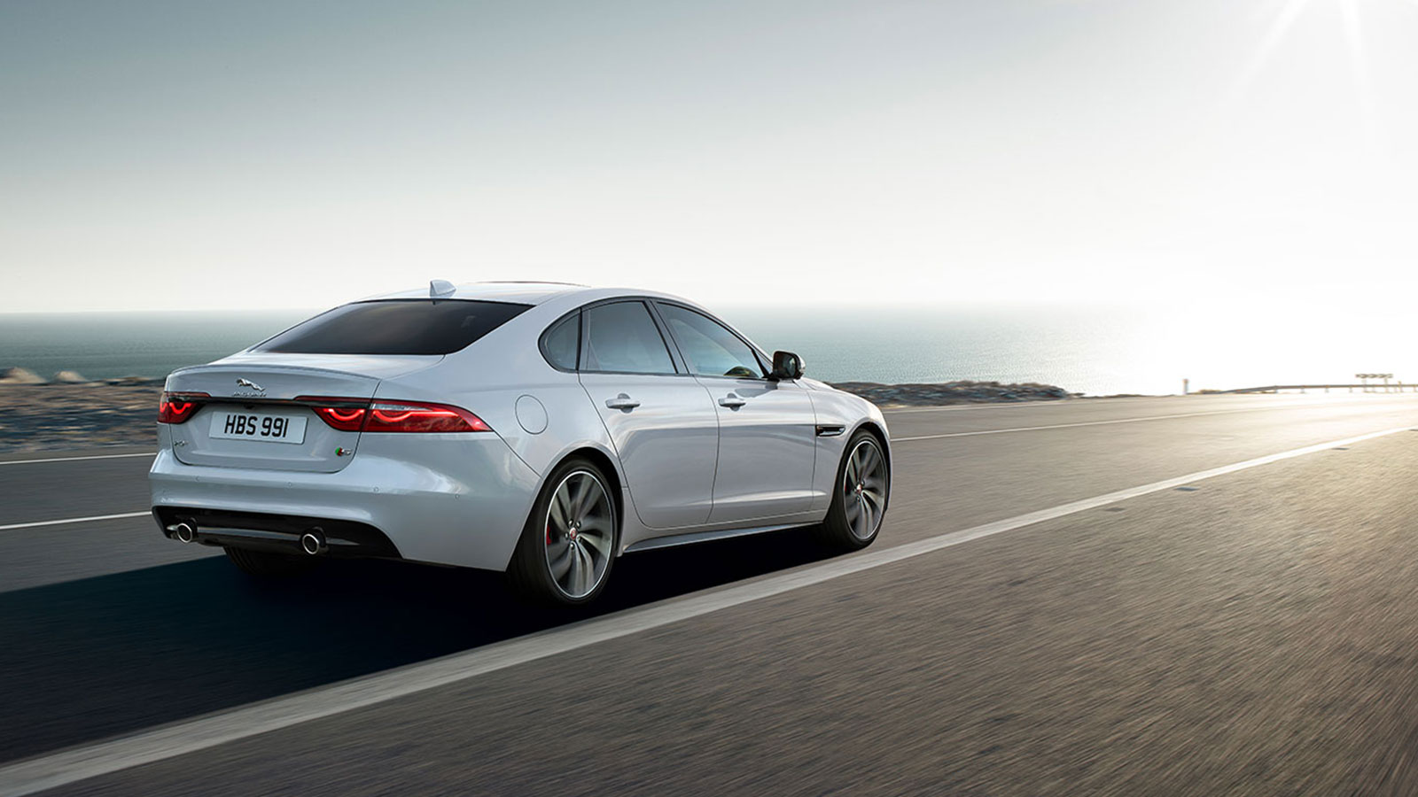 Rear View of Jaguar XF Drivien On Road.