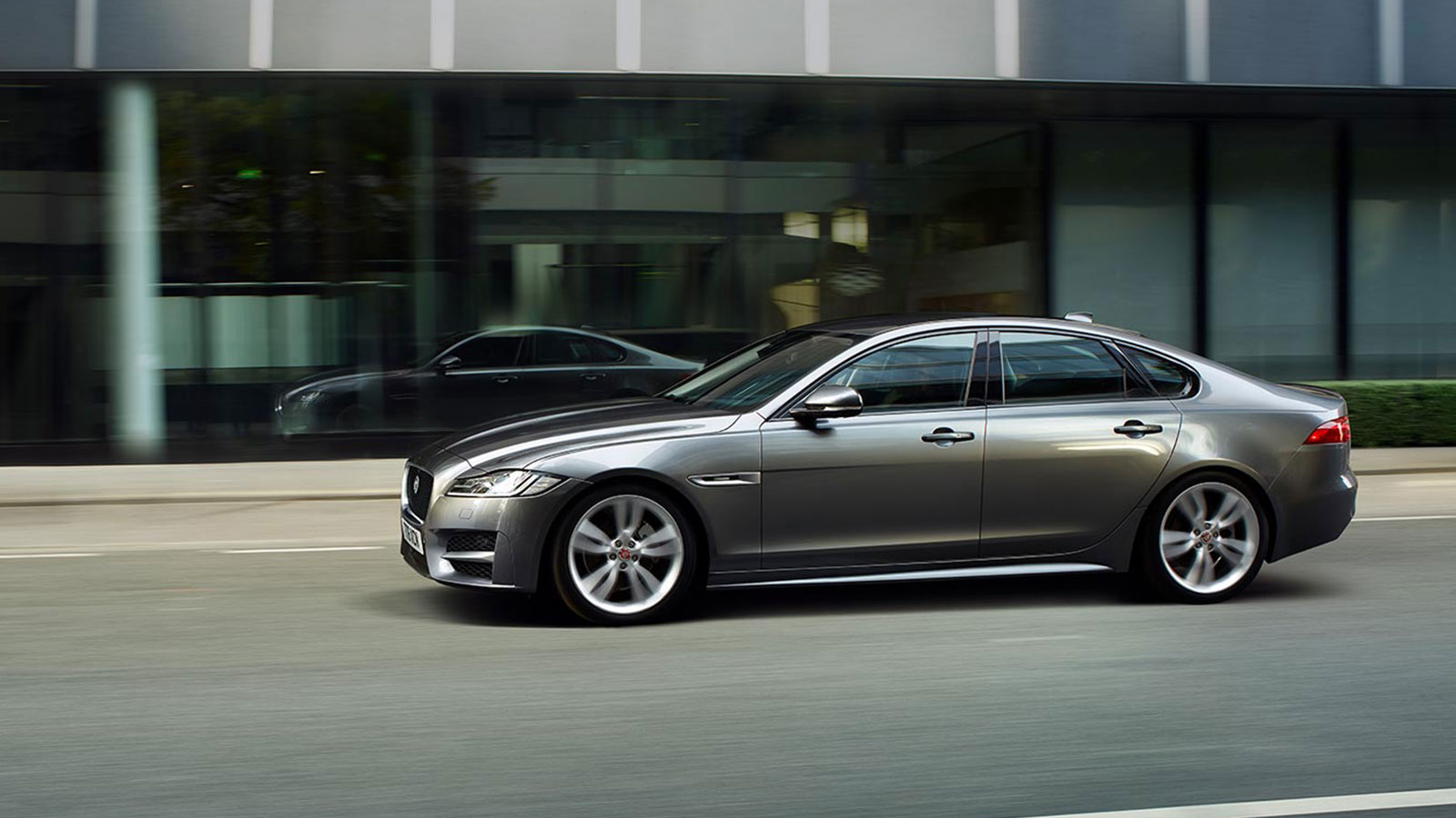 Jaguar XF Driving In City side View.