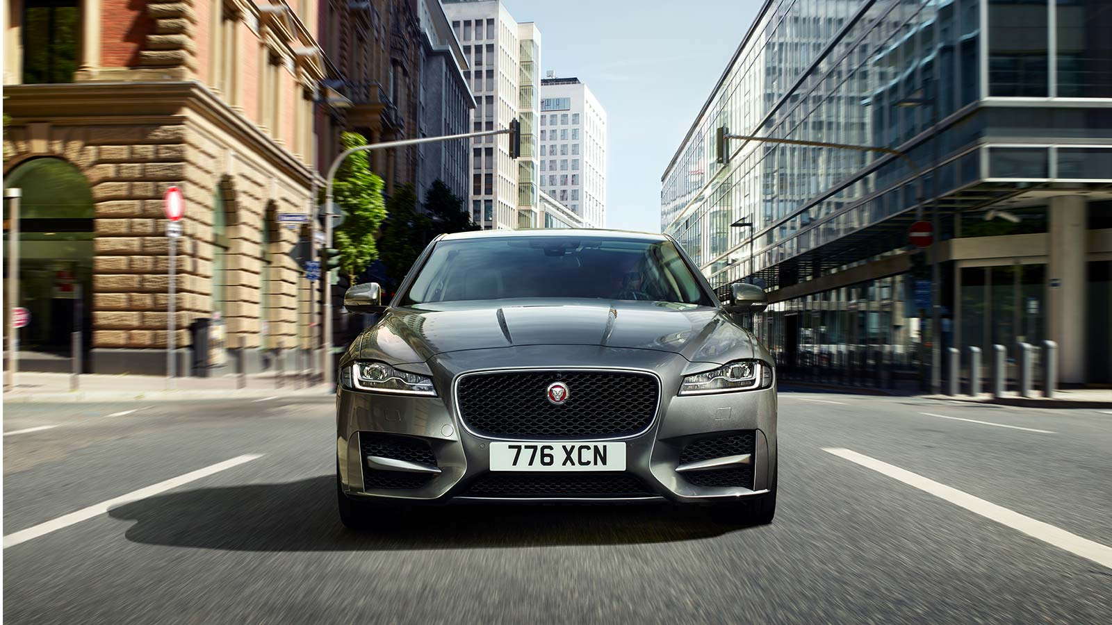 Front view of a Jaguar XF Driving on a road.