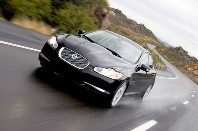 Black Jaguar XF Driving on road.