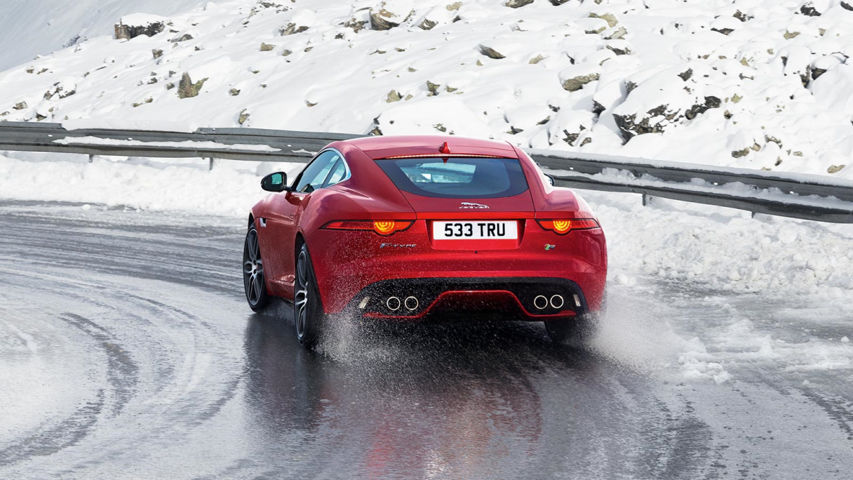 Jaguar F-TYPE in red from behind going round a snowy bend.