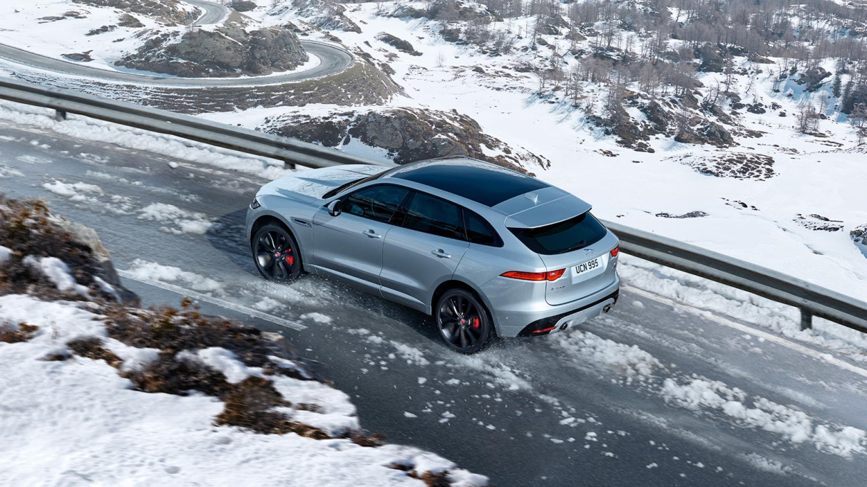 Jaguar F-PACE in grey from behind driving in the snow.