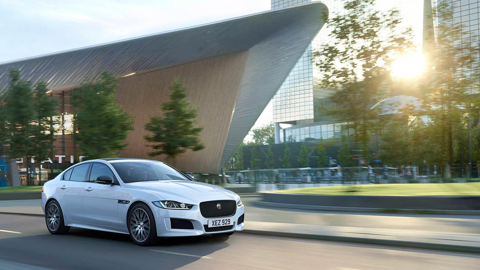 Jaguar XE S parked on a gravel driveway, surrounded by bushes and trees.