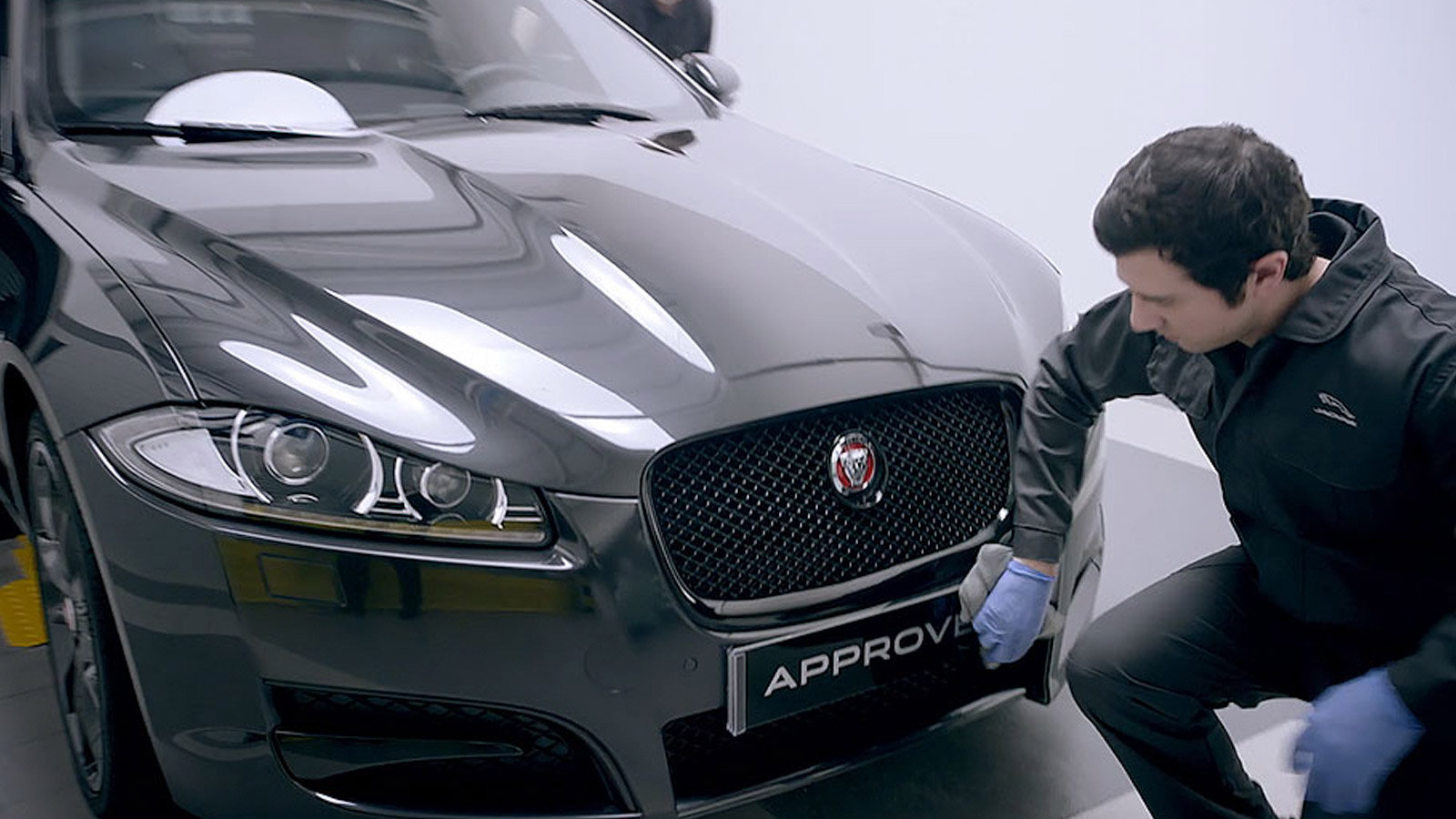 A Jaguar mechanic wiping the front of an approved used Jaguar vehicle.