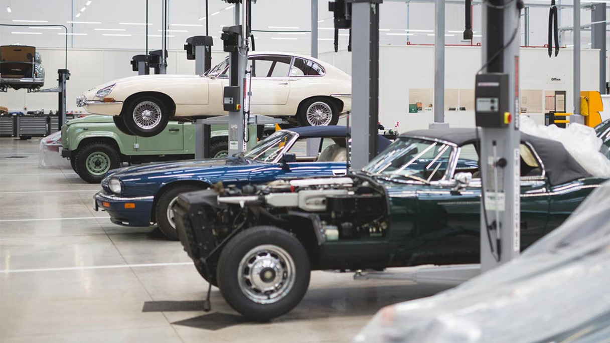 Various classic vehicles in individual bays inside the Jaguar Land Rover Classic Works Facility.